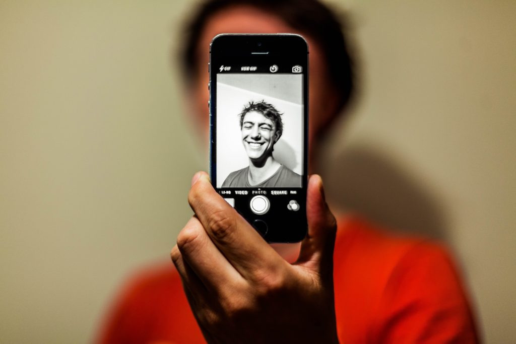 a man taking a black-and-white selfie , smile, red t-shirt,, antoine beauvillain