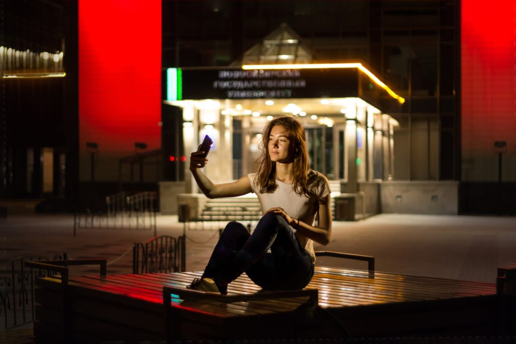 a girl sitting on a bench and taking a selfie, night, lights, red walls, alla biriuchkova
